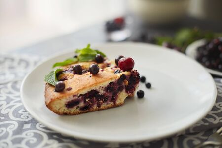 Piece of pie with blueberries, rasberry and mint for dessert on a white plate, napkin. Pieces of delicious homemade cake Reklamní fotografie