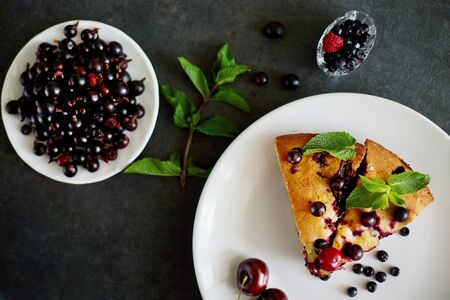 Piece of pie with blueberries, rasberry,cherries and mint for dessert on a white plate, napkin. Pieces of delicious homemade cake