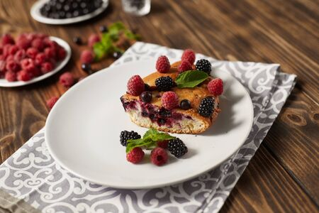 Piece of pie with blueberries, rasberry and mint for dessert on a white plate, napkin on a wooden boards background