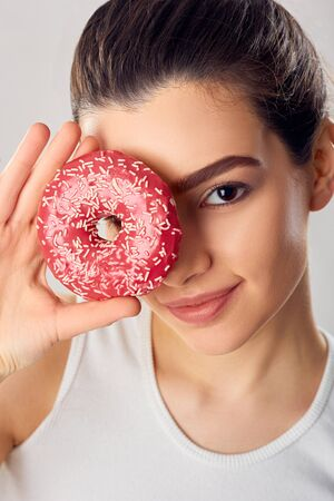 Young Girl Covered Her Face with Pink Donut. Brunette Girl Tastes a Donut. Sweets Are Unhealthy Junk Food. Dieting, Healthy Eating, Lifestyle. Weight Loss. Zdjęcie Seryjne
