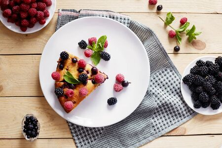 Piece of pie with blueberries, rasberry and mint for dessert on a white plate, napkin. Pieces of delicious homemade cake on a wooden boards background
