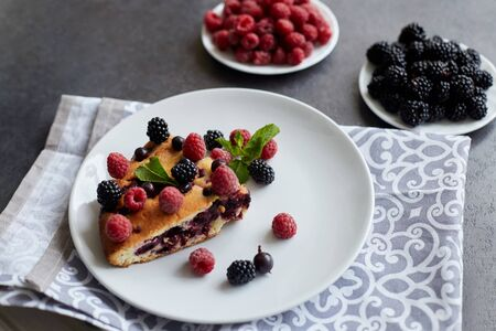 Piece of pie with blueberries, rasberry and mint for dessert on a white plate, napkin. Pieces of delicious homemade cake on a background Reklamní fotografie