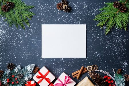 Beautiful Christmas composition on a dark background. Christmas present boxes, snowy fir branches, conifer cones, gift. New Year. Top view, copy space.