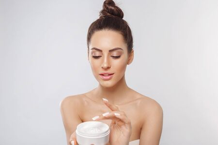 Beauty Woman Face Skin Care. Portrait Of Attractive Young Female Applying Cream And Holding Bottle. Closeup Of Smiling Girl With Natural Makeup And Fresh Skin. Cosmetics.