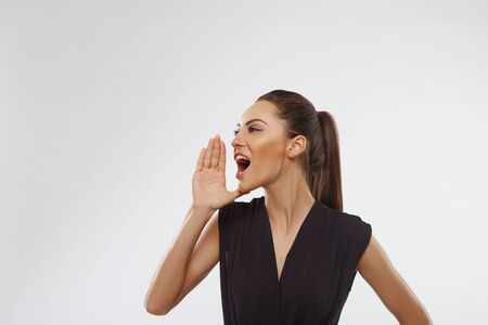 Beautiful young woman over isolated background shouting and screaming loud to side with hand on mouth. Communication concept