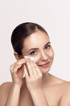 Woman Cleaning Face With White Pad. Beautiful Girl Removing Makeup White Cosmetic Cotton Pad. Happy Smiling Female Taking Off Makeup From Facial Skin With Cosmetic Pad. Face Skin Care.