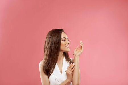 Beautiful model girl with a beige French manicure nail . Fashion makeup and care for hands and nails and cosmetics. Beauty Young Woman with Clean Fresh Skin close up . Skin care face .