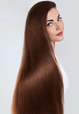 Hair.Beautiful woman with luxurious long hair. Gorgeous Model Girl with Healthy brown smooth shiny straight Hair. Keratin straightening.Treatment, care. Smooth Hairstyle.