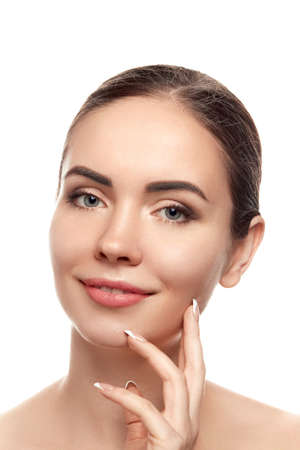 Beautiful Young Woman with Clean Fresh Skin touch own face. Facial treatment. Beauty and spa. Skin Care. Cosmetics.Makeup,
