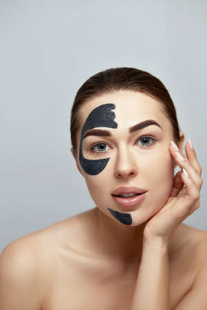 Facial Mask. Beautiful Young Woman with black mask of clay on face .Skin care .Girl model with cosmetic mask. Facial treatment. Moisturizer Spa mask