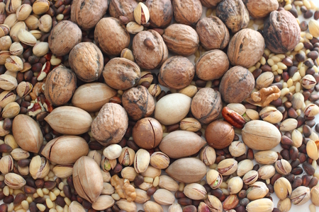 Spilled nuts of different kinds - macadamia, pecans, pistachios, pine nuts, walnut Stock Photo