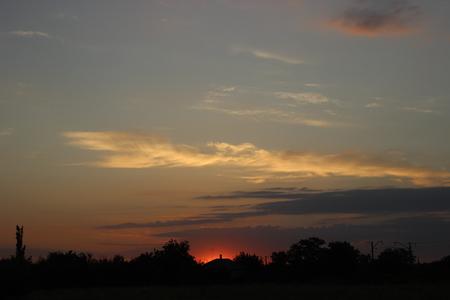 Rural house against the setting sun.