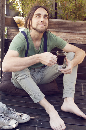 suspenders: Men with suspenders drinking coffee barefoot Stock Photo