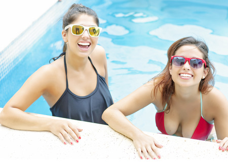 lesbian love: Young beautiful girls enjoying sun and having fun in swimming pool Stock Photo