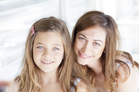 position d amour: Heureuse mère et sa fille mignonne regardant la caméra