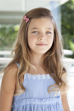 10 to 12 years old: Beautiful blonde girl with blue eyes and light blue dress