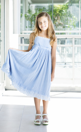 10 12 years: Beautiful blonde girl with blue eyes and light blue dress
