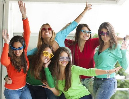 Group of smiling teenagers wearing novelty fun glasses