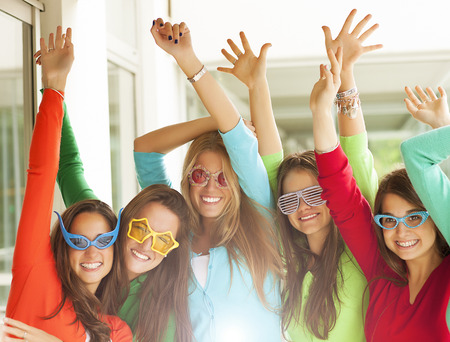 novelty: Group of smiling teenagers wearing novelty fun glasses
