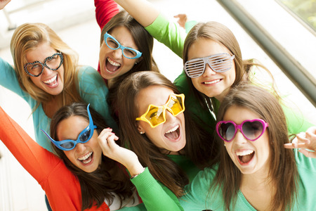 the novelty: Group of smiling teenagers wearing novelty fun glasses