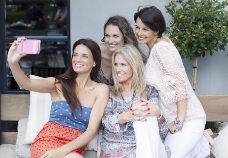 mujeres sentadas: Amigos Felices sexo femenino que toma en selfie Aire libre