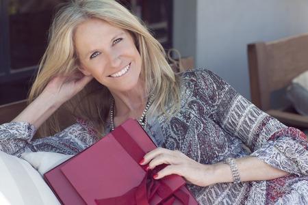 blonde yeux bleus: Heureux Mignon femme moyenne d'âge avec un cadeau en plein air