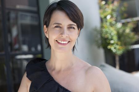 Glückliche lateinische erwachsene Frau im Freien lächelnd