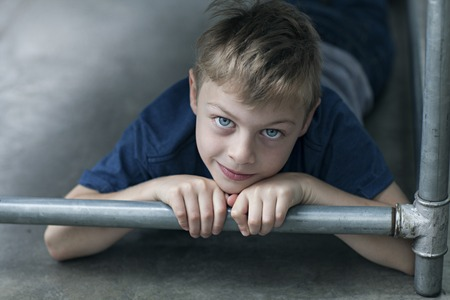 beautiful little boys: boy lying down on floor looking at camera