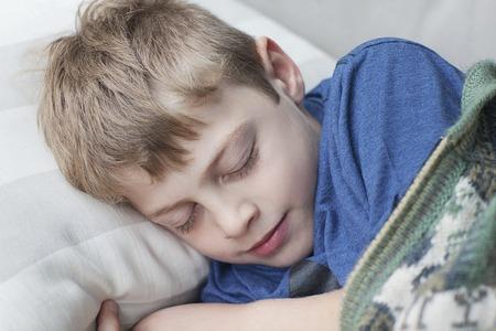 colegiala: rubio ni�o duerme en el sof� en la habitaci�n Foto de archivo