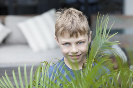 boy in shorts: Smiling boy on a green background outdoors
