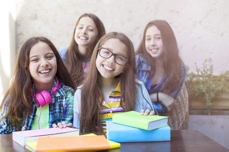 diligente: Retrato de dos ni�as diligentes mirando a la c�mara en el lugar de trabajo con las estudiantes en el fondo