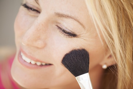 a beautiful blonde woman putting on make up