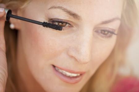 Ritratto di una femmina bellissima mettendo il trucco sugli occhi