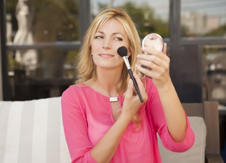 putting: woman putting on makeup shot in outdoors Stock Photo