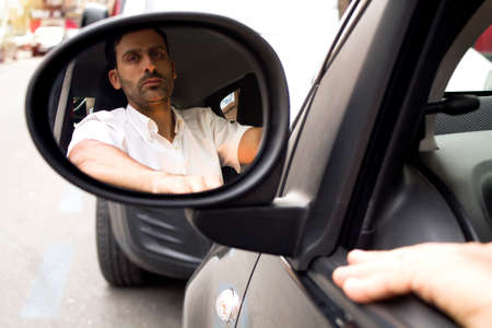 man inside the car with his reflection in the external rear view mirror