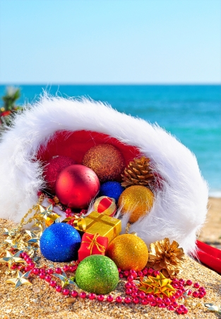 Christmas baubles and gift boxes in the christmas hat on the sand in the seashore