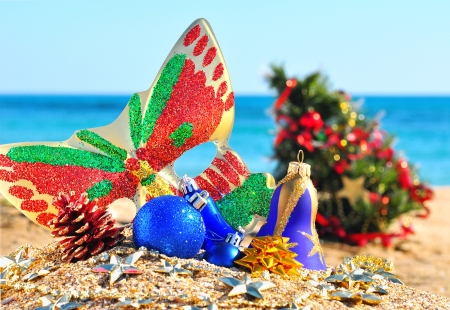 Christmas baubles, face mask, christmas tree on the sand in the beach photo