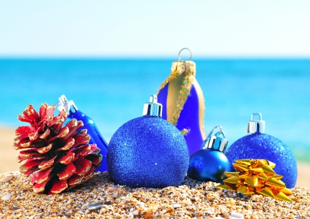 Christmas blue baubles and cones on the sand in the seashore