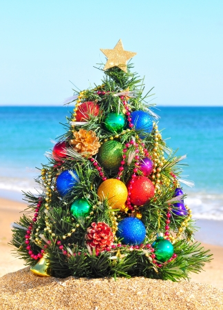 artificial light: Christmas tree on the sand in the beach Stock Photo