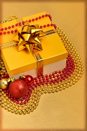 Yellow gift box with christmas baubles and beads around photo