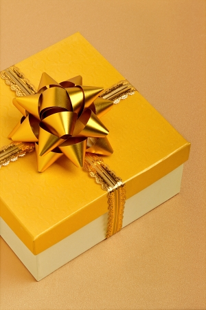 Golden gift box on the beige tablecloth photo