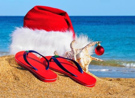 Santa Claus hoed en slippers aan de kust tegen blauwe hemel