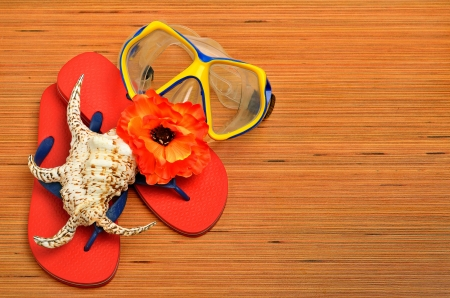 Mask, seashell, flower and flip flop sandals on the wood photo