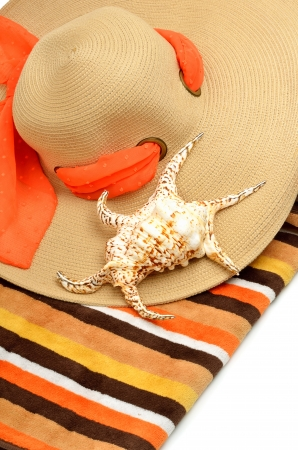 Beach hat, bright towel and a seashell isolated on white photo