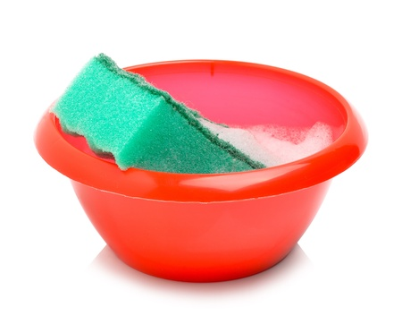 Red bowl and green sponge with foam isolated on white photo