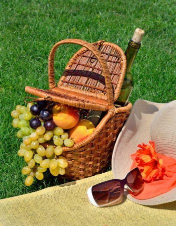 Beach hat, sun glasses, picnic basket with fruits and  bottle of wine on the green grass photo