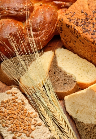 Fresh bread, wheat ears, wheat grains on the wooden background Stock Photo