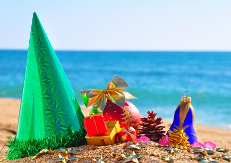 Christmas baubles, gift box and cone on the sand in the seashore photo
