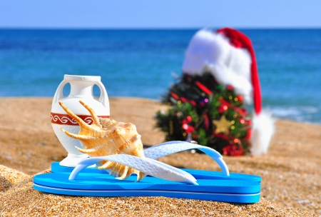 Chrstmas tree, antique vase, slippers on the sand against blue ocean photo