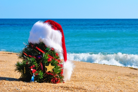 Christmas tree and santa hat on the sand in the beach against the blue ocean
